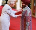 Malkit Singh receiving his MBE from the Queen