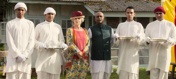 Cynthia (Julie Walters) and Kaiser (Indi Nadarajah) in centre.  Extras surround