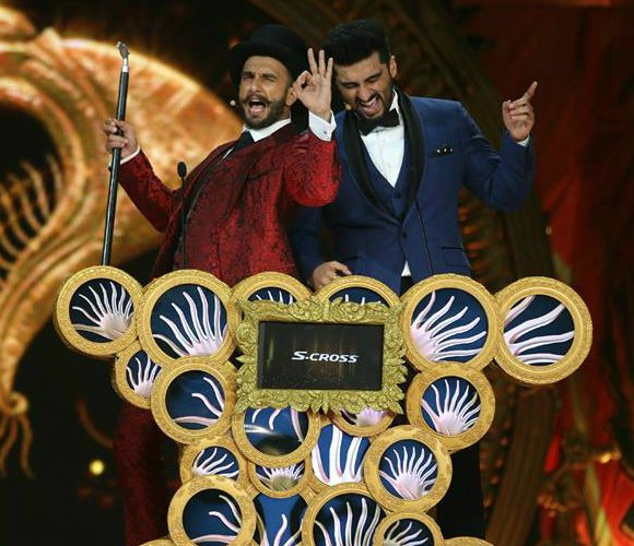 The IIFA host opted for a satin red three piece suit paired with a black top hat.