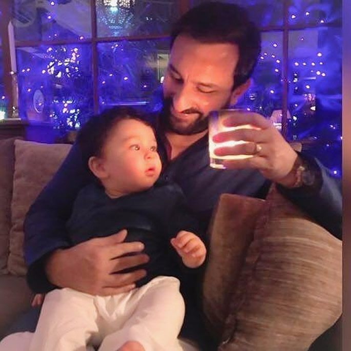 Saif holding Taimur and a candle