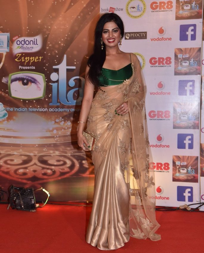 Roshni wearing a green and gold sari
