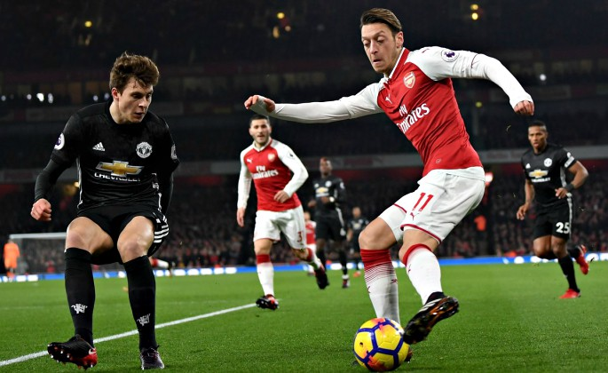 Mesut Ozil attempts to get past Victor Lindelof