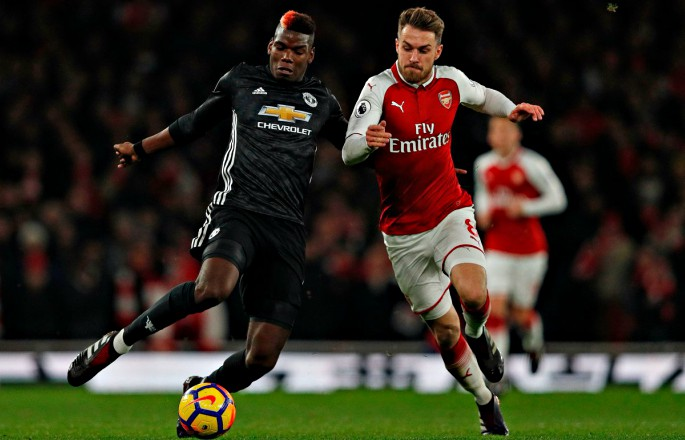 Paul Pogba battles Aron Ramsey for the ball