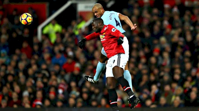 Romelu Lukaku battling for the ball in the air with Vincent Kompany