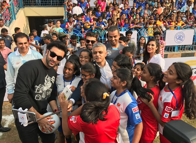 Sadiq and Ranbir taking a selfie with young footballers