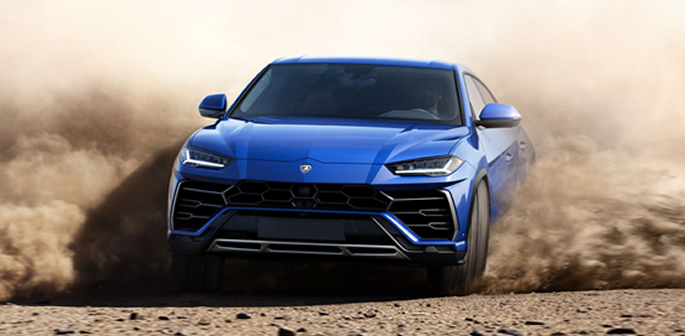 Lamborghini Urus racing through a dirt road