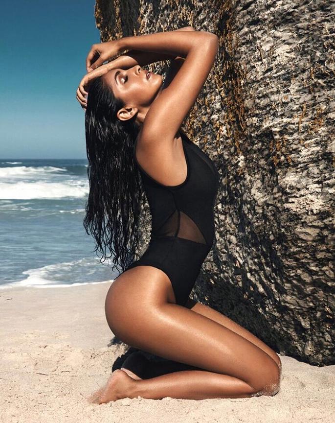 Priyanka kneeling at a beach