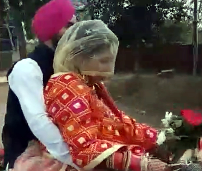 Indian Groom Picks Up His Bride on his Bicycle - side